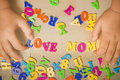Love mom hands of a boy putting plastic alphabets together Stock Photography