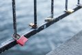 Love padlocks on a bridge in stockholm varios showing the water and iron bars Royalty Free Stock Photo