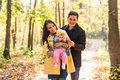 Love parenthood family season and people concept smiling couple with baby in autumn park Stock Photography