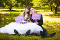 Love in park bride and groom sitting on grass and holding decorative signs Stock Image
