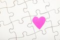 Love puzzle little pink heart on a for your or help copy as the heart is a real paper cutout there is some texture in it Royalty Free Stock Image