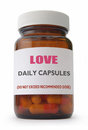 Love remedy daily capsules in a container over a white background Royalty Free Stock Photo