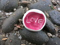 Love on the rocks handmade ceramic rubbing piece in pink enamel with written it so can be used as concept for relationship Royalty Free Stock Images