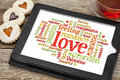 Love and romance word cloud on a digital tablet screen with heart cookies a cup of tea Royalty Free Stock Photos
