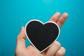 Love sign. Black board heart in woman hands on blue background