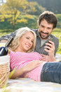 We love this song loving young couple listening to the music on picnic together Stock Image