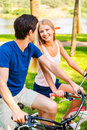 We love spending time together beautiful young smiling couple riding their bicycles in park and looking at each other Stock Images