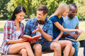We love spending time together four happy young people while sitting outdoors Stock Images