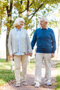 We love spending time together happy senior couple holding hands and smiling while walking by park pass way Royalty Free Stock Image