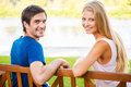 We love spending time together rear view of beautiful young loving couple sitting on the bench and looking over shoulder with Royalty Free Stock Images