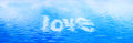 Love text in clean water waves. Banner, panorama. Royalty Free Stock Photo