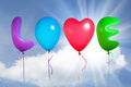 Love text shaped color balloons against sky background Stock Images