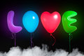 Love text shaped color balloons black background with smoke Royalty Free Stock Photography