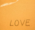 Love - text written by hand in sand on a beach Royalty Free Stock Photo