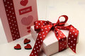Love theme ft card with pink gift and red polka dot ribbon and hearts. Royalty Free Stock Image