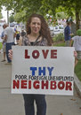 Love thy neighbor asheville north carolina usa august woman at a moral monday rally holds a sign saying poor foreign unemployed on Royalty Free Stock Photography