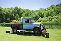 Love truck an old blue pickup by a pond full of straw salt and a wooden crate full of flowers Stock Photo