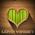 Love vegan wooden porthole heart shape with green vegetables interior on wooden wall and written Stock Images