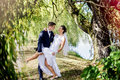 Love among the weeping willows wedding outdoor session groom holds leg of bride and she is holding her hand on his neck they look Royalty Free Stock Photo