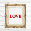 Love word in golden vintage photo frame on white brick wall,Love concept Royalty Free Stock Photo