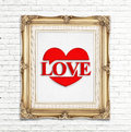 Love word and heart icon ( Saying love) in golden vintage photo frame on white brick wall,Love concept Royalty Free Stock Photo