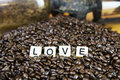 Love the word set in coffee beans on wood counter with antique grinder Stock Photo