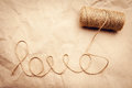 Love word written by a thread from the spool on a paper background Royalty Free Stock Photography