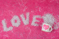 Love wording arrange by bead and white glass with heart shape on pink mulberry paper background Stock Images
