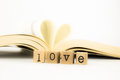 Love wording and a book with heart shape closeup emotion concept idea Royalty Free Stock Photography