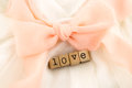 Love wording and dress with peach bow ribbon closeup white soft textiles wedding concept idea Stock Image