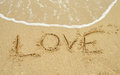 Love written in sand the a warm tropical beach Stock Photos