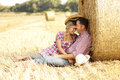 In love young couple on haystacks in cowboy hats a Royalty Free Stock Image