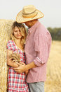 In love young couple on haystacks in cowboy hats a Royalty Free Stock Photos