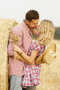 In love young couple on haystacks in cowboy hats Royalty Free Stock Photo