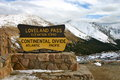 Loveland pass continental divide sign at in colorado with snow capped mountains in the background Stock Photos