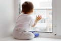 Lovely baby age of year looks out of window in winter on wintertime Royalty Free Stock Image