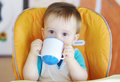 Lovely baby boy drink from baby cup age of year Stock Images