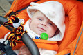 Lovely baby boy outdoor in orange stroller Royalty Free Stock Photos