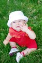 Lovely baby looks up sitting on grass in summer age of months Royalty Free Stock Photo