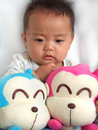 Lovely baby and toy monkeys Royalty Free Stock Images