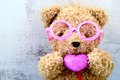 Lovely bear doll wearing pink glasses and holding pink heart sha Royalty Free Stock Photo