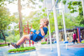 Lovely blond little boy on a swing in the park. Adorable boy having fun at the playground Royalty Free Stock Photo