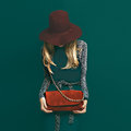 Lovely blond model in fashionable red hat and a red clutch on gr green background Stock Photos