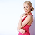 Lovely blond woman smiling while posing on white background in pink dress Royalty Free Stock Photos