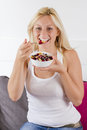 Lovely blonde woman eating cereals with fruit at breakfast portrait of Royalty Free Stock Image