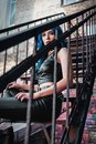 Lovely blue-haired rock girl informal model, dressed in black leather pants and topic sits on ladder Royalty Free Stock Photo