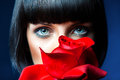 Lovely brunette behind red rose in studio Royalty Free Stock Photos