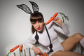 Lovely bunny woman in rabbit costume with carrots Royalty Free Stock Images