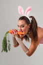 Lovely bunny woman in rabbit costume with carrots Royalty Free Stock Image
