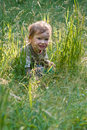 Lovely child plays to a grass Royalty Free Stock Photo